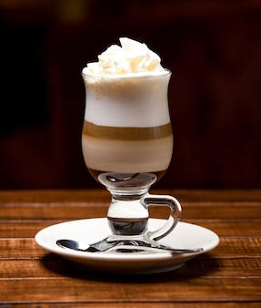 Cup of hot latte with froth and cream
