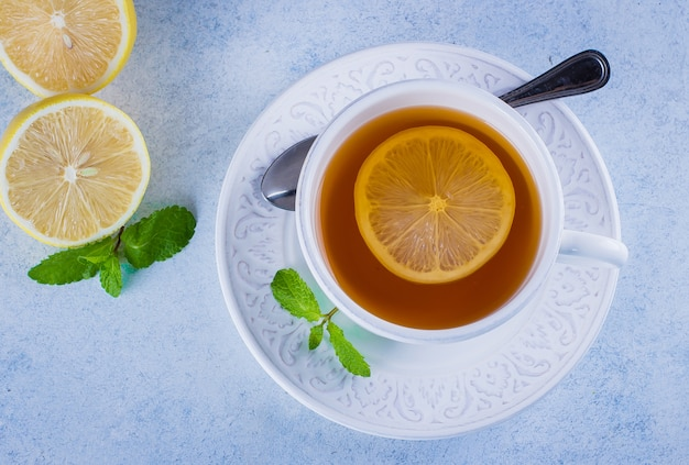 Cup of hot lemon tea with mint