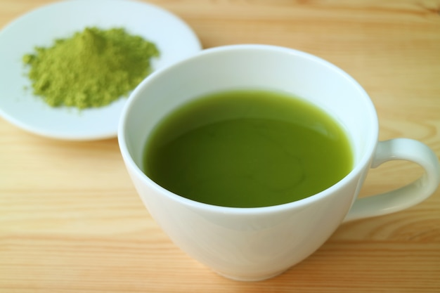 Cup of hot matcha green tea served on wooden table with blurry plate of matcha tea powder in background