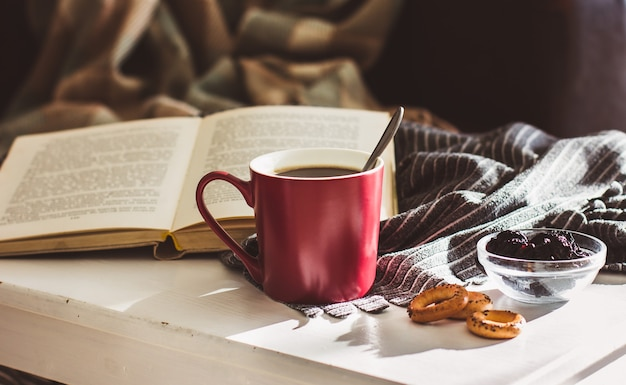 A cup of hot steaming coffee in a red mug, cookies, and an old book on a white wooden table