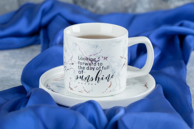 Cup of hot tea on blue cloth.