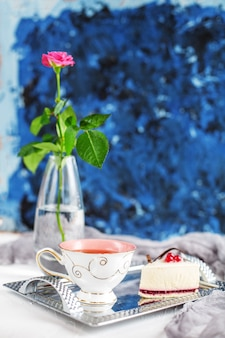 A cup of hot tea and cake on a blue background. breakfast.