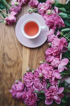 A cup of hot tea is on a table with many peonies