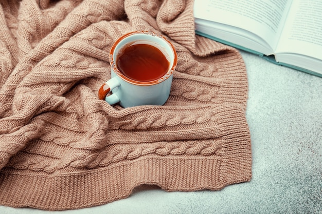 Cup of hot tea, open book and warm knitted blanket