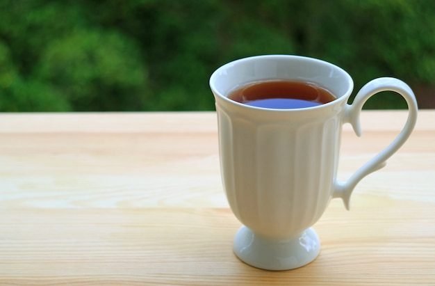 Cup of hot tea on outdoor terrace wooden table, with blurred background of green foliage