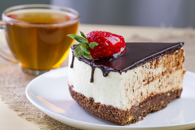 A cup of hot tea and a slice of sweet cake with fresh strawberries and dripping chocolate glaze in a white plate
