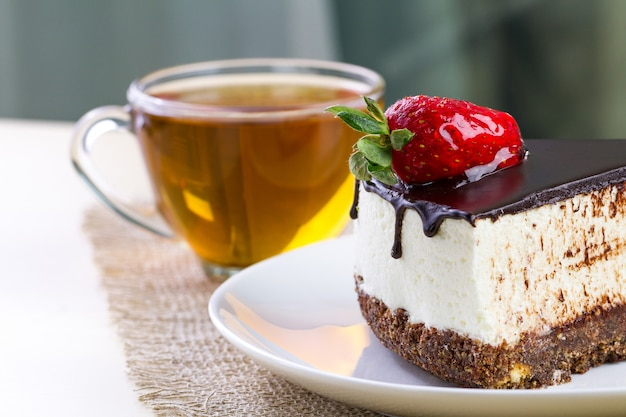 A cup of hot tea and a slice of sweet cake with whipped cream, fresh strawberries and dripping chocolate glaze in a white plate.