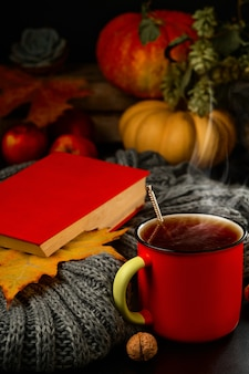 Cup of hot tea, steam rises from the drink. book, warm scarf and autumn leaves on the table.