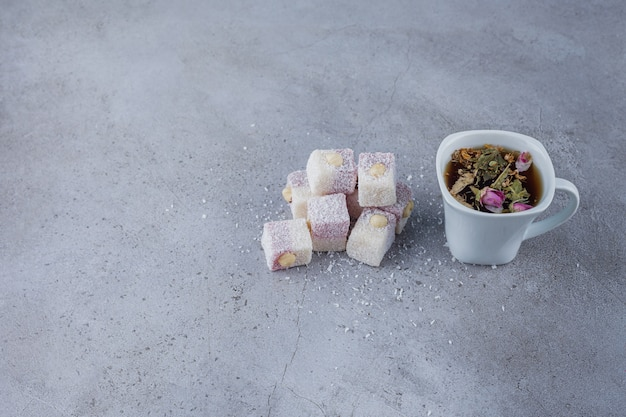 Cup of hot tea and sweet delights with nuts on stone background.