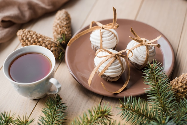 A cup of hot tea with christmas gingerbread, a branch of a spruce tree on a wooden background