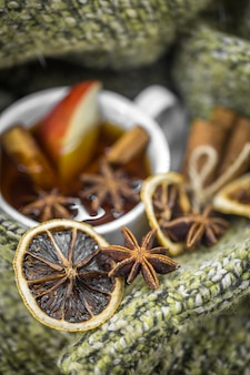 Cup of hot tea with cinnamon sticks and delicious dried citrus fruit
