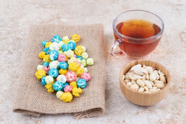 Una tazza di tè caldo con caramelle colorate