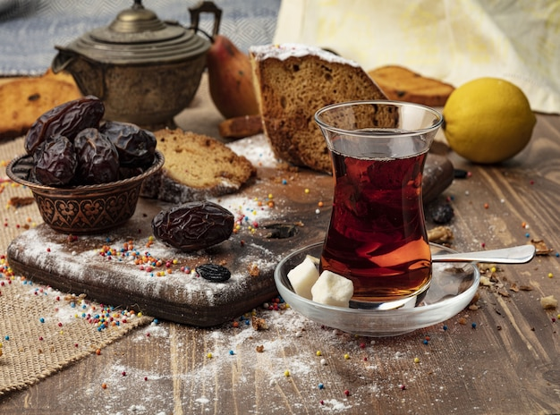 A cup of hot tea with dates on wooden background.