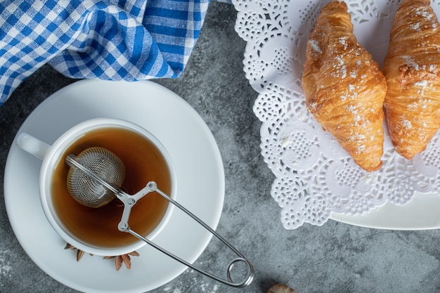 Cup of hot tea with delicious croissants on marble surface.