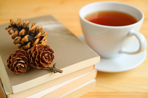 Cup of hot tea with dry pine cones on stack of books on natural color wooden table
