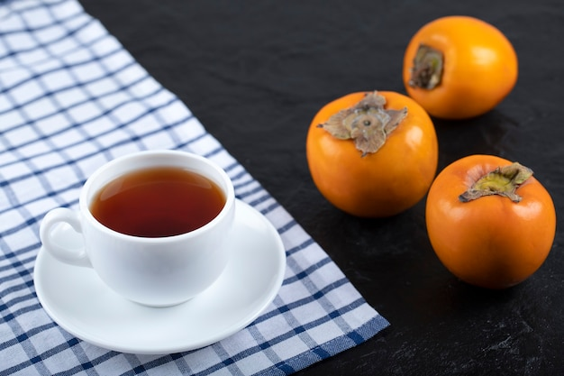 Cup of hot tea with fresh persimmons on black.