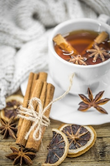 A cup of hot tea with lemon, a cinnamon stick and a spoonful of brown sugar on wood