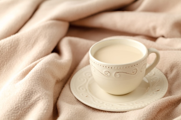 Cup of hot tea with lemon dressed in knitted warm winter scarf on wool, soft focus