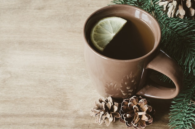 A cup of hot tea with lemon on a rustic table.