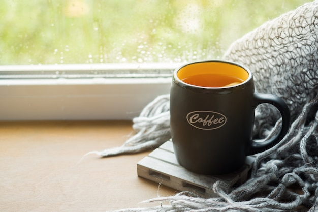Cup hot tea with lemon on the windowsill woolen plaid