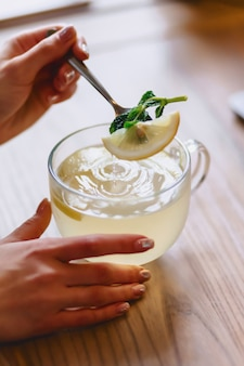 A cup of hot tea with mint and lemon mixes the girl with a spoon