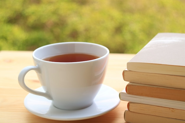 Cup of hot tea with pile of books on wooden table with blurred background of plants in garden