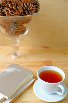 A cup of hot tea with stack of books on wooden table and a glass compote of dry pine cones