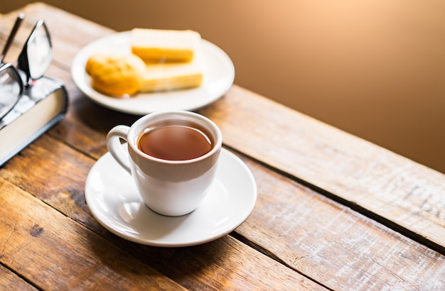 Cup of hot tea with steam and wafers snack, old thick book with glasses on old table floor and blur window light in living room