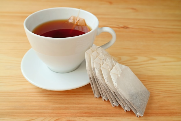 Cup of hot tea with tea bags served on wooden table