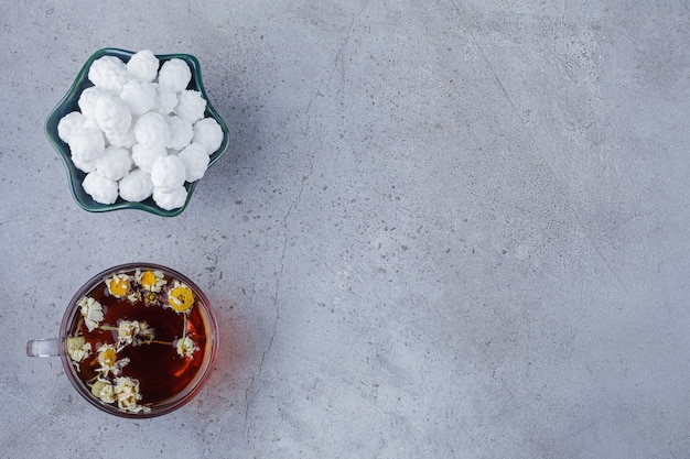 Cup of hot tea with white bowl of white candies on stone background.