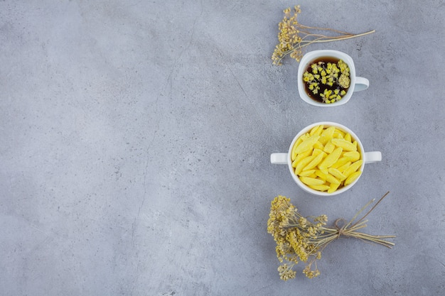 Cup of hot tea with white bowl of yellow candies on stone background.