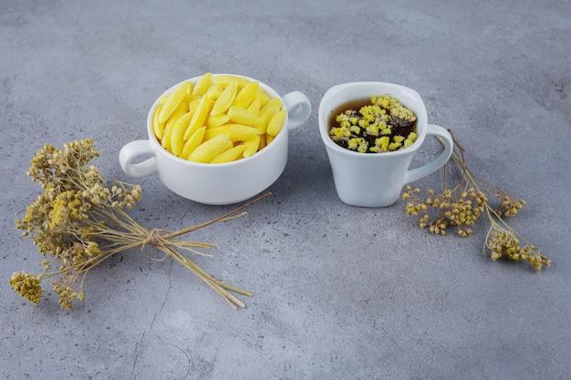 Tazza di tè caldo con una ciotola bianca di caramelle gialle sulla pietra.