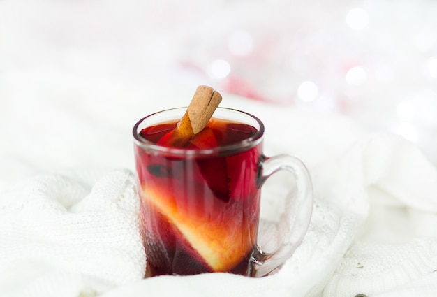 Cup of hot winter drink with knitted sweater on the table, closeup. horizontal photo