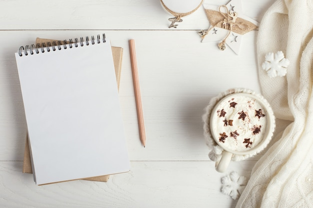 A cup of hot winter drink, with whipped cream and powder with an asterisk, a notebook, white snowflakes and a knitted scarf on a wooden table