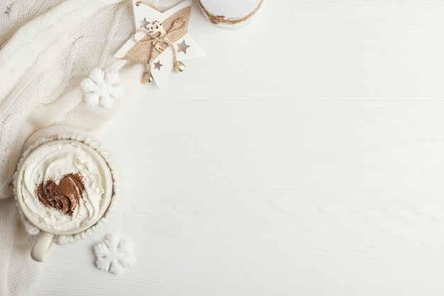 A cup of hot winter drink with whipped cream and scarf on a wooden table