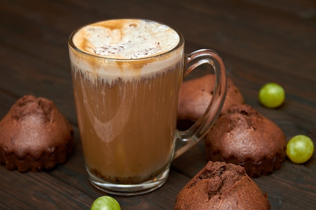 A cup of iced coffee with homemade chocolate muffins and grapes