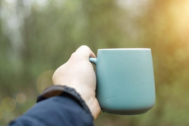 녹색 숲의 배경에 대해 남자의 손에 컵.