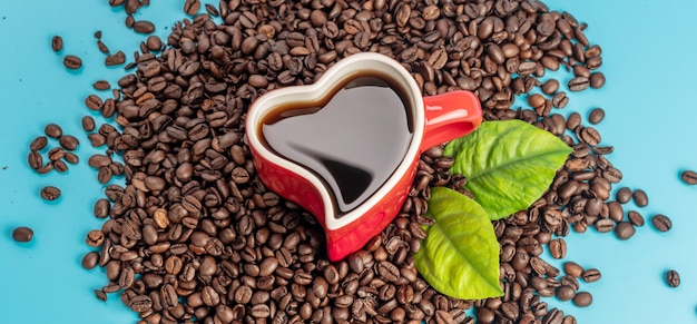 Чашка в форме сердца с кофе и кофейными зернами