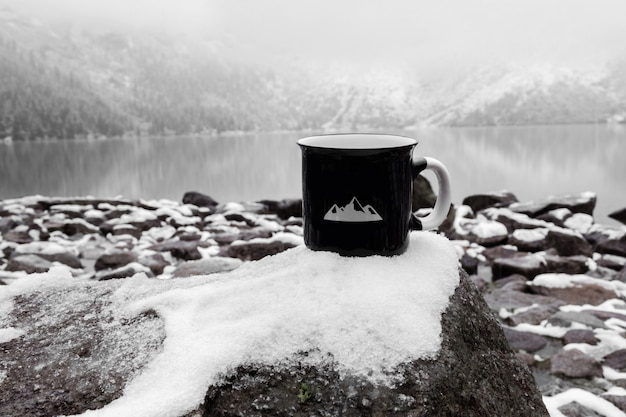 Cup for the inscription. black mug on the background of a mountain lake in winter