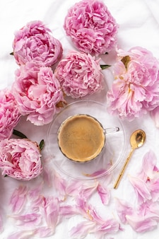 Cup of instant coffee on the table with pink peonies under the lights