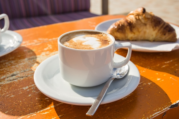 Cup of invigorating cappuccino and a croissant for breakfast