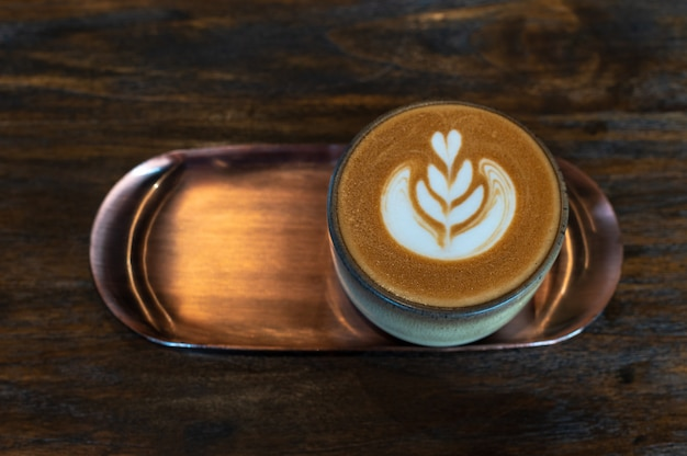 A cup of latte art coffee in brass plate on wooden table