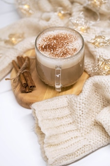 Cup of latte coffee with cinnamon white sweater and christmas garland lights