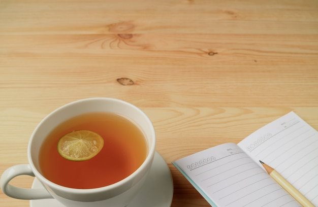 Cup of lemon tea and lined note papers with pencil on natural color wooden table, with free space