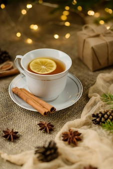A cup of lemon tea, shot with selective focus, against a backdrop of christmas decorations.