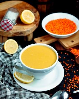 A cup of lentil soup served with lemon