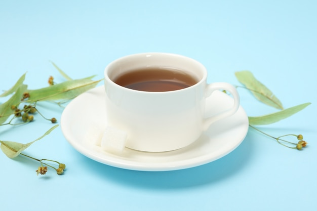 Cup of linden tea on blue, close up