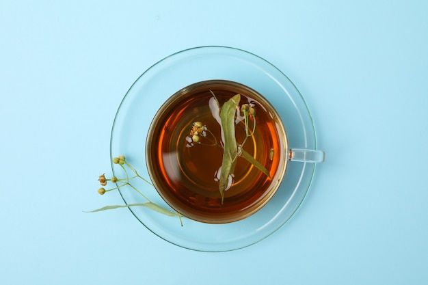 Cup of linden tea on blue, top view