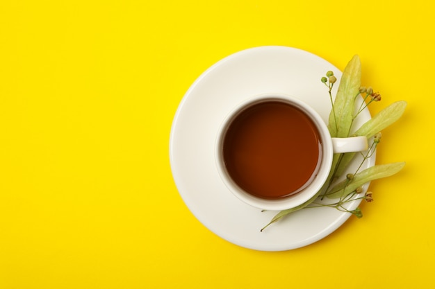 Cup of linden tea on yellow, top view