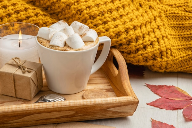 Cup of marshmallows with present and candle next to sweater